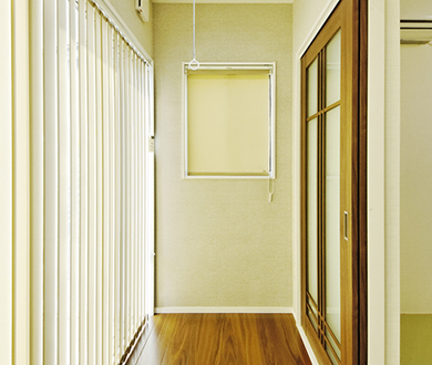 縦スクリーンカーテンで温かな光が差すサンルームには物干し金具を装備。
