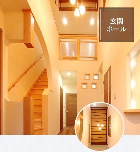 二階の大きな窓から光が注ぐ吹き抜けの玄関ホール。階段横の床柱と丸みのある壁は、和らぐ雰囲気でお客様を迎ます。