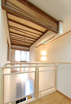 吹き抜け天井も照らす階段上の照明。天井には木目が浮き上がる浮造り仕上げ、古民家で使われるすす竹、おさ欄間など和洋折衷の空間。