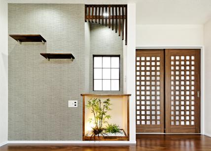 落ち着いたアクセントクロスとテレビの配置を考えたお洒落なニッチ。建築白石オリジナルのピーラ材とパイン材の飾り棚で趣きのある空間を演出。