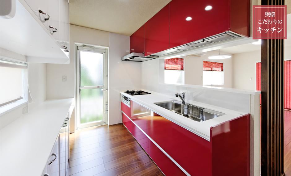 奥様こだわりの赤いカラーが印象的なクリナップの乾燥機付きシステムキッチン。