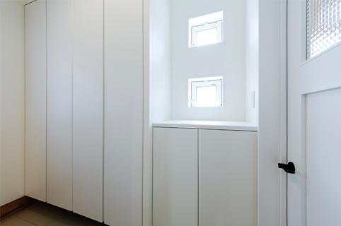 アーチの間仕切り奥にはスッキリと白い扉の大容量の玄関収納。