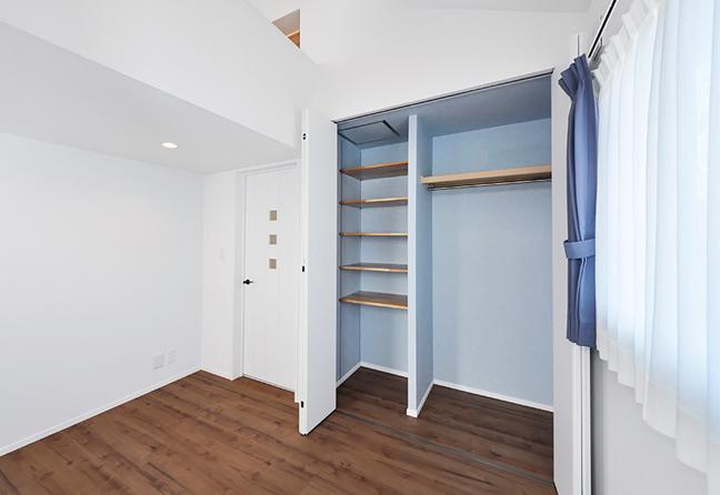 クローゼットの中はカーテン色にあわせたアクセントクロス。オリジナルの仕切りで収納しやすい棚を装備。