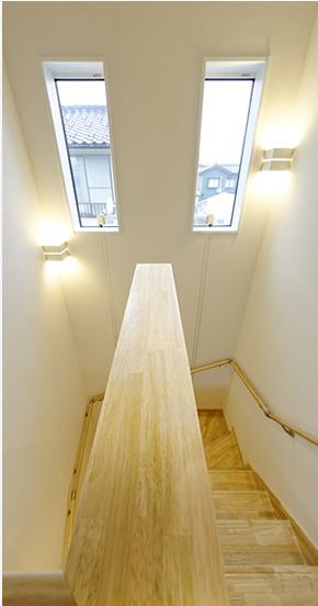 明るい吹き抜けの階段、天井近くに大きな二つの窓