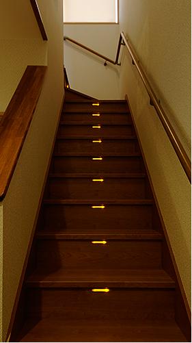 夜、ほんのり優しい灯りが足元を照らす LIXIL の木質階段。