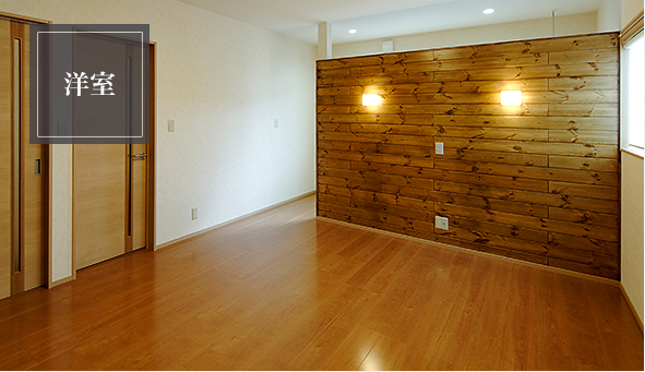 ピーラ材の大きな間仕切りのある広い洋室。