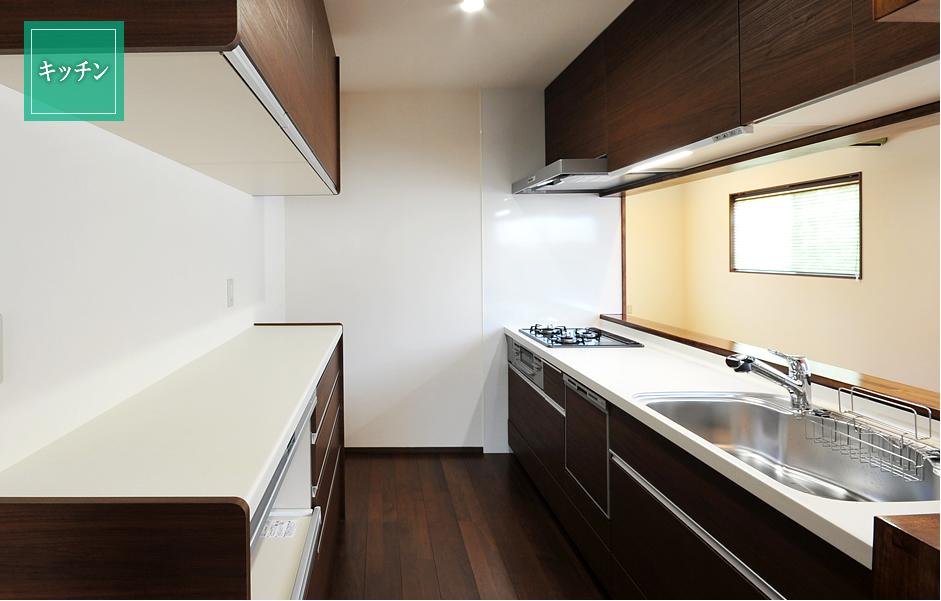 ウォールナット色の LIXIL システムキッチンに蒸気排出ユニット付の家電収納。