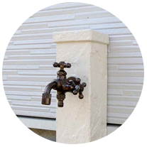 ウォールナット色のモダンな玄関横には、お洒落な立水栓(外水道)を設置。