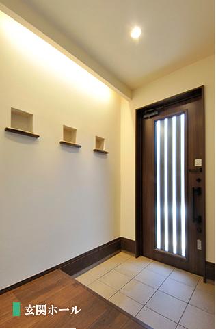 優しい光でお客さまを迎える間接照明とニッチのある玄関。