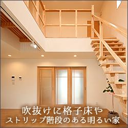 吹抜けに格子床やストリップ階段のある明るい家