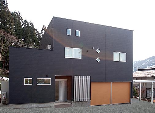 高級感のあるウッド調のシャッター、黒とシルバーのキューブ型の外観